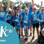 """A group of children wearing blue Monash Children's Hospital shirts stand together, raising their hands and smiling. Text overlaying the picture in the bottom left corner reads """"Walk 2021: Register today!"""""""